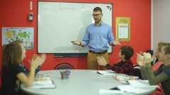 Happy teacher greets students in the classroom Stock Footage