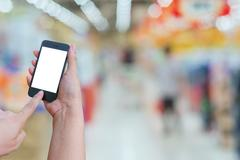 Woman hold and touch screen mobile phone while shopping in super market bac.. Kuvituskuvat