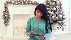 Attractive young woman with long hair using tab in christmas interior Stock Footage
