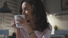 Happy young woman wearing pajama sitting with tea/chocolate/coffee mug, smiling. Stock Footage