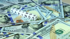 """Word from cubes """"savings"""" on the spinning surface of American dollars Stock Footage"""