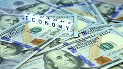 """Word from cubes """"economy"""" on the spinning surface of American dollars Stock Footage"""