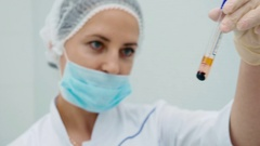 Doctor show a tube with plasma blood in laboratory Stock Footage