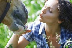 Woman and horse together at paddock Stock Photos