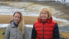 Close up shooting of two blonde tourists, smiling and walking in geothermal area Stock Footage