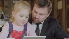 Cute little girl in a cafe with her dad playing on tablet computer Stock Footage
