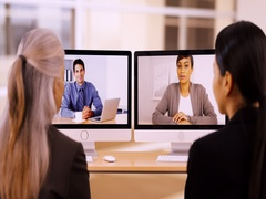 Two businesswomen have a conference call with their co-workers Stock Footage