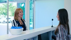Eldery woman talking with receptionist in clinic Stock Footage