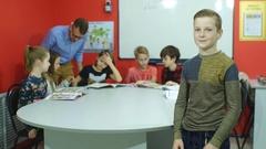 Redhead schoolboy stands near a school board smiling Stock Footage