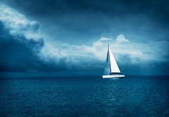 White Yacht Sailing in Stormy Sea. Dark Photo. Kuvituskuvat