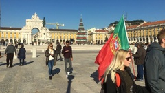 Man Waves Portuguese Flag In Downtown Lisbon, Praça Do Comercio Stock Footage