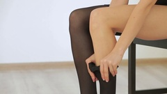 Sexy woman putting on stockings in lingerie Stock Footage