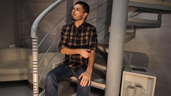 Young bearded man in checkered shirt sitting on stairs enjoys his new home and Stock Footage