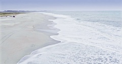 Aerial over man driving a quad bike on a beach, Haast, New Zealand Stock Footage