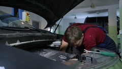 Mechanic is fixing the car engine under the hood Stock Footage