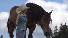 4K Farmer Child Looking a Grazing Horse, Cowboy Girl Playing and Pasturing Stock Footage