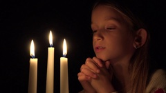 4K Sad Child by Candles, Prayer Girl in Night, Pensive Upset Kid Portrait, Face Stock Footage