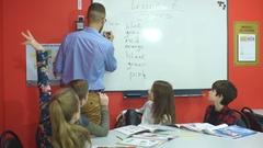 Teacher writing on the board in an elementary school class Stock Footage