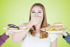 Fat woman rejects high calorie food Stock Photos