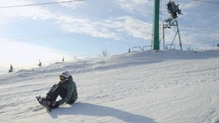 Woman sitting on a slope wears snowboard in slowmotion. 1920x1080 Stock Footage