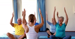 Trainer assisting senior citizens in practicing yoga Stock Footage