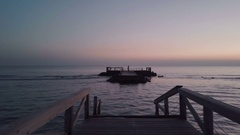 A small wooden bridge collapsed in the middle of the sea, autumn sunset. Aerial Stock Footage