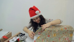 Woman packing present with Gift Wrapping Paper, preparing for New Year Stock Footage