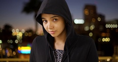 A hooded young girl smiles at the camera Stock Footage