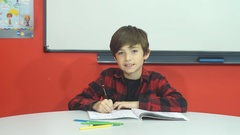 Beautiful school boy is sitting in class and smiling at camera Stock Footage
