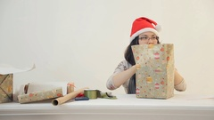 Asian brunette woman sits wraps new year present box in studio Stock Footage