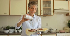 Senior woman sprinkling freshly baked tart with powdered sugar Stock Footage