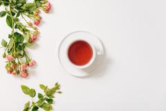 Branch of roses lying near the tea cup Stock Photos