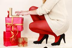 Woman with many gift boxes opening golden box with jewel pearls Stock Photos
