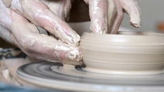 Man with her hands dub wall jug, which she sculpts out of clay on circle macro Stock Footage