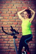 Active woman using exercise bike at the gym. Stock Photos