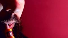 Man with beard vaper smokes vaping closeup Stock Footage
