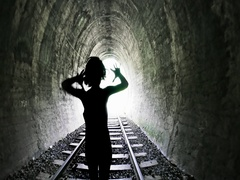 Man goes by railway tracks through dark tunnel toward bright light in the end Stock Footage