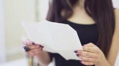Portrait of stylish young woman with brown hairs reading letter in apartment Stock Footage