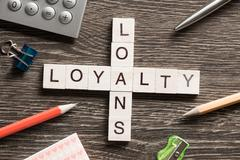 Loans and loyalty crossword puzzle collected of game wooden cubes Stock Photos