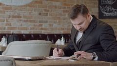 Businessman in cafe fills working papers Stock Footage