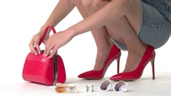 Woman putting things into handbag. Stock Footage