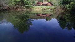 Aerial Shot across Pond to Wood Cabin Lodge in Background Stock Footage