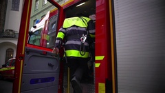Firefighters in uniform getting in firetruck, going on a mission, dangerous job Stock Footage