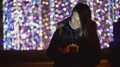 Beautiful Woman in Winter Dark Coat With Smartphone in the Night City on Stock Footage