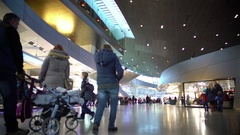 People with children walking in large shopping mall, lots of stores, weekend Stock Footage