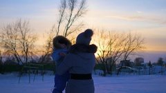Girl plays with baby at sunset in winter time Stock Footage