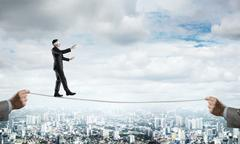 Business concept of risk support and assistance with man balancing on rope Stock Photos