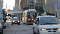TTC streetcar travelling along street at rush hour Stock Footage