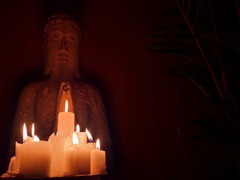 Ancient statue of Buddha spiritual candle light in darkness of Buddhist temple Stock Footage
