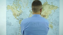 A man looks at a map of the world Stock Footage